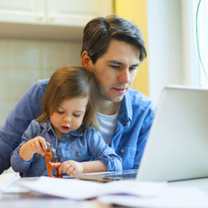 Man working from home on laptop with daughter